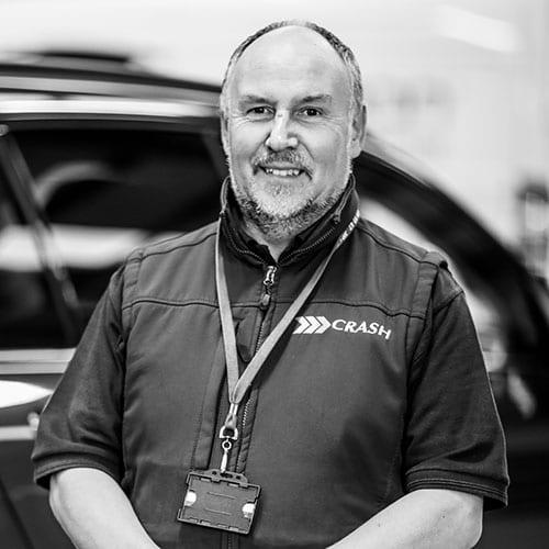John Glover CRASH Staff Profile smiling behind a car